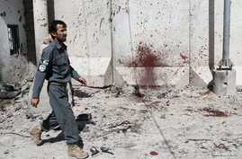 FILE - An Afghan policeman walks past a bloodstained wall after Taliban fighters stormed a government compound in Kandahar province, July 9, 2014. At least 16 police personnel were killed overnight in a Taliban attack in the province's Maiwand distri...