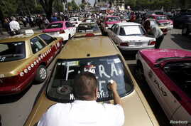 """FILE - A local taxi driver paints """"Uber out"""" on the back window of his car during a protest in Mexico City, May 25, 2015."""