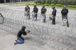 A Cambodian woman takes a photo of riot police standing behind bard wire at Freedom Park in Phnom Penh, Cambodia, May 1, 2014.