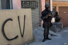 """FILE - A soldier stands guard next to a wall tagged with the acronym """"CV"""" identifying the criminal organization """"Comando Vermelho"""" or Red Command, during an operation at the Rocinha slum, in Rio de Janeiro, Brazil, Tuesday, Oct. 10, 2017."""