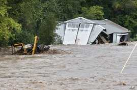 Overflowing St. Vrain River swamps structure and piece of heavy machinery following overnight flash flooding near Lyons, Colo., Sept. 12, 2013.