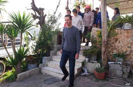 In this photo released on Friday, Dec. 29, 2017 by the official Facebook page of the Syrian Presidency, Syrian President Bashar Assad with members of the first family, visit wounded veterans at their houses over the holidays, in the central province