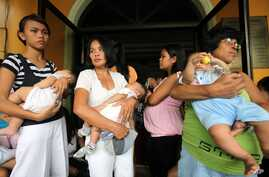 Mothers cuddle their babies as they undergo medical checkup at Cainta Town Hall at Cainta township, Rizal province east of Manila, Philippines, October 8, 2009.