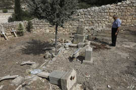 Father Antonio Scudu, caretaker of Saint Stephen Church in the Beit Jamal Salesian monastery, looks at overturned crosses in a graveyard that has reportedly been vandalised near the central Israeli town of Beit Shemesh, west of Jerusalem, Oct. 18 201