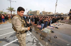 A member of the Iraqi security forces stands guard as worshippers conduct open-air Friday prayers in Baghdad's Sadr City, Iraq, Oct. 30, 2015.