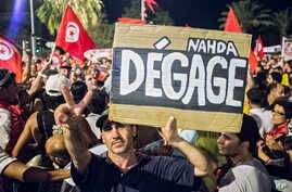 """A protester holds a banner reading """" Nahda go away""""  during a demonstration against Tunisia's Islamist-led government, Augusr 6, 2013 in Tunis."""
