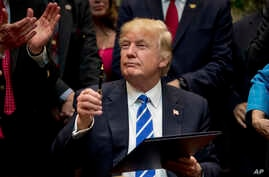 In this March 27, 2017, photo, President Donald Trump holds up a pen he used to sign one of various bills in the Roosevelt Room of the White House in Washington.