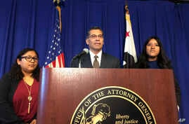 California Attorney General Xavier Becerra is flanked by Rosa Barrientos, of East Los Angeles, left, and Eva Jimenez, of Visalia, right, as he announces a lawsuit challenging the Trump administration's decision to end a program that shields young imm