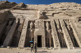 A picture taken on November 25, 2017 shows tourists exiting the Nefertari complex at the ancient Egyptian temple of Abu Simbel, some 1120 kilometres south of the Egyptian capital Cairo. The UNESCO World Heritage Site temples, originally carved out of