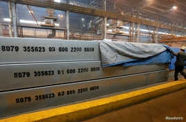 An employee removes a covering of 13-meter aluminium ingots weighing 34 tons (74,957 pounds) at the foundry shop of the Rusal Krasnoyarsk aluminium smelter in Krasnoyarsk, Siberia, July 27, 2016.