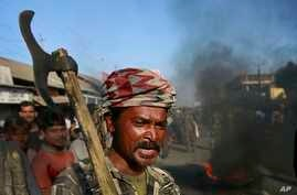 An Indian tribal settler shouts slogans as he blocks a road with others in protest against the attack by an indigenous separatist group in Shamukjuli village in India's Assam state, Dec. 24, 2014.
