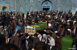 FILE - Afghan men attend a funeral ceremony of an International Committee of the Red Cross (ICRC) employee, who was killed  by gunmen in Mazar-i-Sharif, Afghanistan, Feb. 9, 2017.