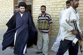 Shiite cleric Muqtada al-Sadr (L) - whose political party called December 26, 2011, for dissolution of Iraq's parliament and new elections in another move that could escalate country's growing sectarian crisis - steps from an office building in Najaf