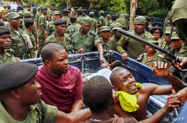 FILE - Zambian police officers apprehend supporters of the opposition United Party for National Development outside the presidential election result center at the Mulungushi International Conference Center in Lusaka, Jan. 21, 2015.