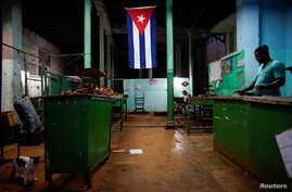 "FILE - A Cuban flag decorates a subsidized state store, or ""bodega,"" where Cubans can buy basic products with a ration book they receive annually from the government, in downtown Havana, Cuba, Nov. 22, 2017."