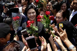 Thailand's former Prime Minister Yingluck Shinawatra, center, receives flowers from her supporters at the Supreme Court after making her final statements in a trial on a charge of criminal negligence in Bangkok, Thailand, Tuesday, Aug. 1, 2017.