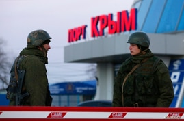 Armed men, believed to be Russian soldiers, stand outside the civilian port in the Crimean town of Kerch, March 3, 2014.