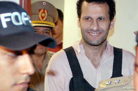 FILE - Lebanese-born businessman Assad Ahmad Barakat, a suspected member and fundraiser of the Islamic group Hizbollah, leaves the Justice building under escort of police officers in Asuncion, Nov. 18, 2003.