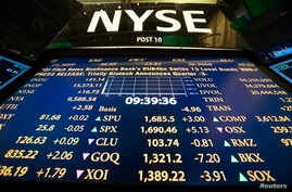 The New York Stock Exchange logo stands above a board displaying stock prices shortly after the beginning of trading, July 30, 2013.