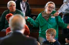 Heaven Chamberlain, of Des Moines, Iowa, right, asks Rep. David Young, R-Iowa, a question during a town hall meeting, April 12, 2017, in Des Moines, Iowa