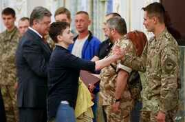 Newly-released Ukrainian pilot Nadiya Savchenko, center left, is congratulated by fellow servicemen in the Presidential Office in Kyiv, Ukraine, May 25, 2016. Ukrainian President Petro Poroshenko is second left. Russia released Savchenko as part of a