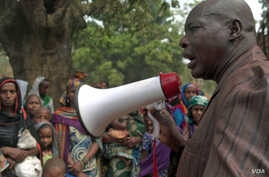 Ibrahim Abaka, the president of an internally displaced persons camp, uses a megaphone to organize the distribution of food aid in Bambari, Central African Republic, Jan. 2017.