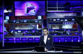 FILE - Television host Nelli Agirba gets ready for a live broadcast at Rustavi 2 TV station in Tbilisi, Georgia, Oct. 2, 2015.