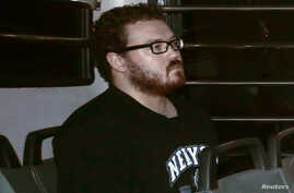 Rurik George Caton Jutting, a British banker charged with two counts of murder after police found the bodies of two women in his apartment, sits in the back row of a prison bus as he arrives at the Eastern Law Courts in Hong Kong, November 24, 2014.