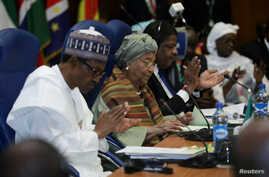 Nigeria's President Muhammadu Buhari, left, Liberia's President Ellen Johnson Sirleaf, center, and Marcel de Souza, president of the ECOWAS Commission, attend the Ordinary Session of the ECOWAS Heads of State and Government in Abuja, Nigeria, Dec. 17