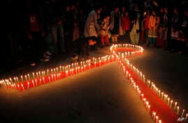 "Nepalese women and children from ""Maiti Nepal"", a rehabilitation center for victims of sex trafficking, light candles on the eve of World AIDS Day in Kathmandu, Nepal, Monday, Nov. 30, 2015."