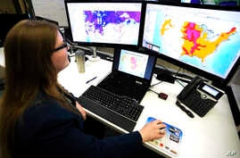 Whitney Flynn, a physical scientist at the National Water Center in Tuscaloosa, Ala., works on computer screens showing flood predictions and other information on March 21, 2019.
