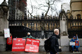 A man passes by pro-Brexit protesters and an anti-Brexit demonstrator outside the Houses of Parliament in London, Britain, March 14, 2019.