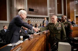 Senate Armed Services Committee Chairman Sen. John McCain, R-Ariz., left, welcomes Marine Corps Commandant Gen. Robert B. Neller, center, and Sgt. Major of the Marine Corps Ronald L. Green on Capitol Hill in Washington, Tuesday, March, 14, 2017, prio