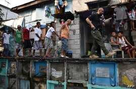 An agent (R) of Philippine Drug Enforcement Agency (PDEA) escorts suspects during a raid at an informal settlers' area inside a public cemetery in Manila on March 16, 2017.