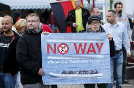File photo of supporters of the far-right National Democratic Party (NPD) holding a placard and a German flag during an anti-immigration march in Riesa, Germany, September 9, 2015. European far right parties have called refugees streaming into the re