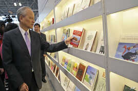 Cui Tiankai, Ambassador of China to the United States, inspects a book as he tours the China pavilion at BookExpo America, May 27, 2015, in New York.