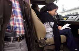 FILE - Jineth Bedoya, a journalist working for El Espectador, takes notes under the watch of a bodyguard as she prepares to leave the newspaper's building in Bogota in an armored car, Friday, Dec. 22, 2000. Bedoya was kidnapped, beaten and raped in A