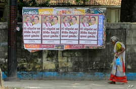A Sri Lankan woman walks past a notice board covered with posters carrying portraits of President Maithripala Sirisena and newly appointed Prime Minster Mahinda Rajapaksa at a street in Colombo, Sri Lanka, Sunday, Oct. 28, 2018.