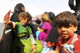 A family fleeing the violence in Mosul, Iraq, waits at a checkpoint in the country's Kurdistan region on June 11, 2014.