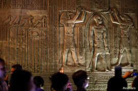 Tourists examine part of the Kom Ombo Temple, southern Egypt,  November 7, 2009. The temple, which dates from about 180 B.C. during the Ptolemaic era with additions made during the Roman period, stands right on the bank of the Nile between Edfu and A