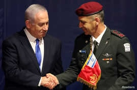 Israeli Prime Minister Benjamin Netanyahu shakes hands with incoming Israeli Chief of Staff Aviv Kohavi during a ceremony whereby he replaces Lieutenant-General Gadi Eizenkot, at the Defense Ministry in Tel Aviv, Israel, Jan. 15, 2019.