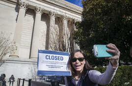 Jamie Parrish, from Minneapolis, takes a selfie in front of the closed sign at the National Archives, Dec. 22, 2018, in Washington. Congress' inability to approve a funding measure that includes money for President Donald Trump's proposed U.S.-Mexico