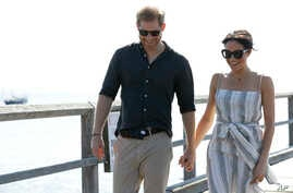 Britain's Prince Harry, left, and Meghan, Duchess of Sussex walk along Kingfisher Bay Jetty during a visit to Fraser Island, Australia, Oct. 22, 2018.
