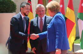 King Abdullah II (C) greets German Chancellor Angela Merkel as she shakes hands with Crown Prince Hussein at the Royal Palace in Amman, Jordan, June 21, 2018.