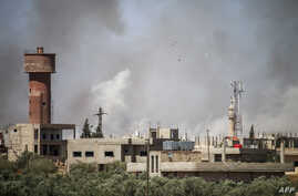 Smoke plumes rise from regime bombardment on the town of Al-Mulayhah al-Sharqiyah in the eastern Daraa province countryside in southern Syria, June 21, 2018.