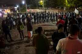 Supporters of presidential candidate Salvador Nasralla gather as police stand guard near the institute where election ballots are being recounted, as they protest what they call electoral fraud, in Tegucigalpa, Honduras, Dec. 1, 2017.