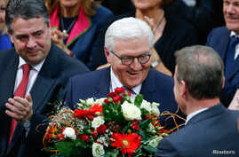 German president-elect, Frank-Walter Steinmeier, receives flowers after the first round of voting of the German presidential election at the Reichstag in Berlin, Feb. 12, 2017.