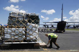 Personnel unload supplies from a New Zealand C130 aircraft in Port Vila, Vanuatu, March 18, 2015.