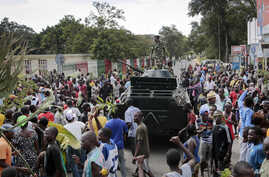 Demonstrators celebrate what they perceive to be an attempted military coup d'etat, with army soldiers riding in an armored vehicle in the capital Bujumbura, Burundi, May 13, 2015.