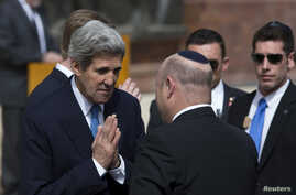 U.S. Secretary of State John Kerry (L) greets an Israeli official before a wreath-laying ceremony marking Israel's annual day of Holocaust remembrance, at Yad Vashem in Jerusalem, Apr. 8, 2013.